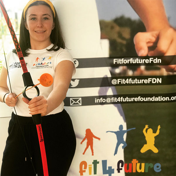 Fit 4 Future Foundation Staff member, Alice Nobbs holding an archery bow and arrow.