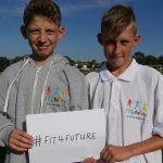 Two young boys promoting the Fit 4 Future Foundation charity hashtag