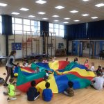 Children playing parachute games at the Fit 4 Future Foundation School Holiday Activities Camp