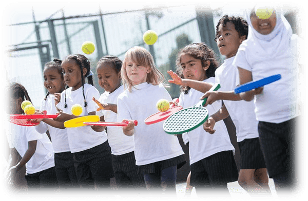 Primary school children practising tennis skills during tennis PE lesson with Fit 4 Future Foundation PE Coach.